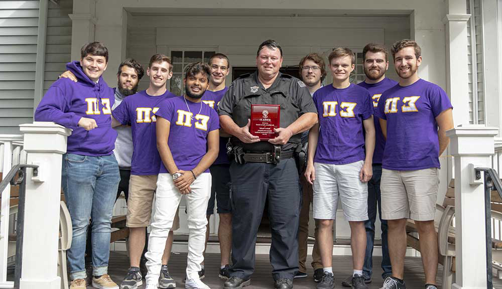 Officer Robert V和al holds his award with brothers from Sigma Pi outside of their fraternity house.